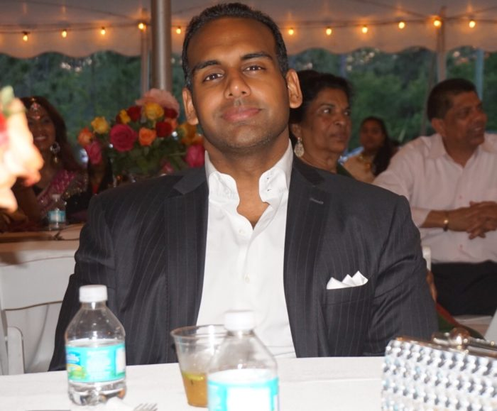 Paul Kaulesar wearing a black suit with a white shirt, sitting down at a traditional Indian wedding,