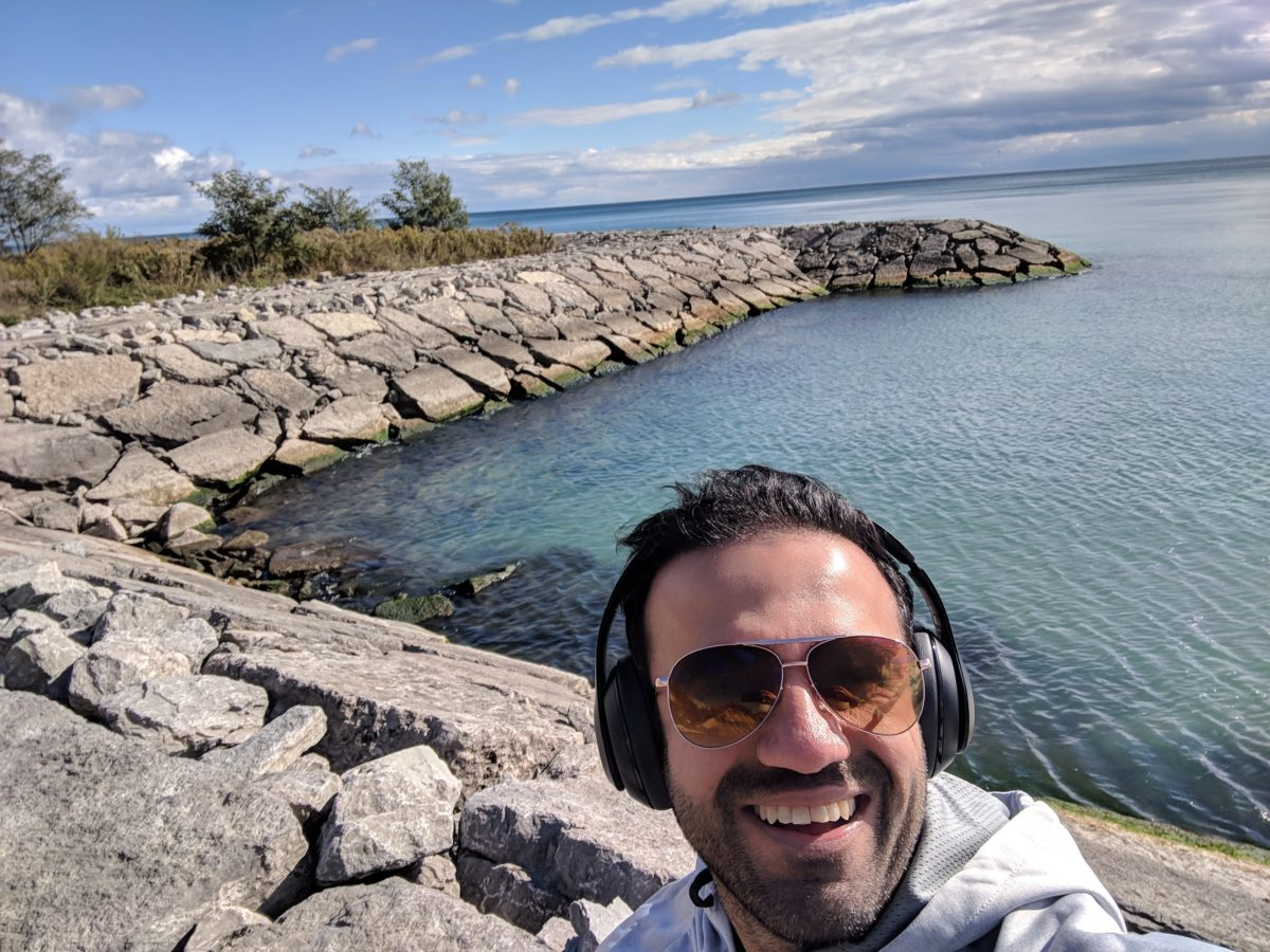 Shabbir Evershine is smiling taking a selfie, wearing sunglasses and has black headphones on his head. He's wearing a grey hoodie sweater. He's standing on rocks at a pier in Toronto. Beautiful blue water surrounds him also with a nice blue and white sky.